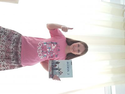 """Karlsruhe Max-Plank-Gymnasium   Mein Foto zeigt mich mit einem T-Shirt wo drauf steht """"a princess in LONDON"""" und mit einem Buch für den Englischunterricht dass mir schon sehr vieles auf Englisch beigebracht hat."""