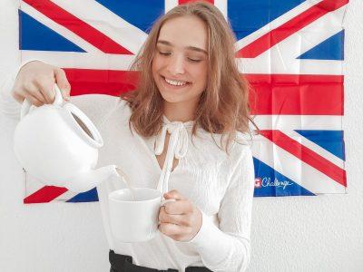 """Langerwehe, Europaschule-Langerwehe (Gesamtschule)  In diesem Foto sieht man mich (Rebeca Pop), wie ich mir """"a cup of tea"""" einschüttel. Das Thema vom Bild ist """"British Style"""". Deswegen habe ich mir ein Britishes Outfit ausgesucht und im Hintergrund sieht man auch noch die UK Flagge."""