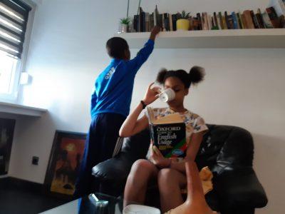 """Hagen, Theodor-Heuss-Gymnasium  Es handelt sich um ein Mädchen ,dass das Oxford Wörterbuch liest und eine Tasse Tee trinkt.Wie die Engländer immer sagen """" It's always time for a nice cup of tea ."""" Der kleine Junge will an einem Buch drankommen."""