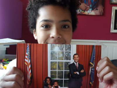 Paderborn, St. Michael Gymnasium.  Me holding a Foto of myself at Madame Tussauds in London with the first African-American President  Barack Obama, at his Oval Office.