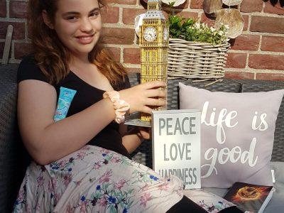 Neuss ,das Erzbischöfliche Gymnasium Marienberg.  Englisch ist mein Lieblingsfach . Das Foto ist auf unserer Terrasse entstanden . Auf dem Bild sieht man den Big Ben als 3D Puzzle , eine Handcreme wo London abgebildet ist , ein Schild mit einem englischem Spruch , ein englisches Buch und ein Kissen mit englischen Wörtern . Verziert ist das Bild mit einer Decke und einer Kiste mit Blumen. Ich sitze auf unserem Sofa auf der Terrasse .