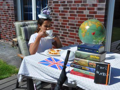 Stadt: Berlin  Schule: Primo-Levi-Gymnasium  Ich war mal besonders kreativ und wollte so viel wie möglich typisch britisches in das Bild quetschen. Hier sieht man die queen Elizabeth Krone, Mohn, Nadelbaumnadeln, englisches Frühstück, english breakfast tea, ein Buch mit schwarzem Humor, die (fast) komplette Harry Potter Reihe, einen Globus, zwei Pence-Münzen, einen englischen Einkaufscheck, einen Regenschirm, eine Teekanne, ich habe höflich meinen kleinen Finger von der Tasse abstehen lassen, ich habe versucht mich englisch anzuziehen und das Foto ist in einer typisch englischen Nachbarschaft. Ich hatte viel Spaß dabei, alles vorzubereiten und wir haben alle gemeinsam darüber gelacht, wie übertrieben typisch britisch das Foto war. Ich möchte natürlich auch gewinnen, aber weniger wegen der Kamera sondern weil ich nur selten gewinne und auch selten die chance dazu habe. Und dieses mal war es eine gute Möglichkeit, denn ich habe viele Ideen und Kunst ist mein Ding. :)  Katherina Vecgaile