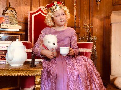 Ich bin Leyla von Ketteler und gehe in Arnsberg auf das St.Ursula-Gymnasium und hier sieht man mich als Queen während der Teatime mit einem kleinen Big Ben auf dem Tisch, einem typisch britischen Hund - dem Foxterrier - und englischen Büchern - u.a. Harry Potter mit entsprechendem Gryffindor-Emblem an der Wand - in gemütlicher Atmosphäre im britischen Stil.