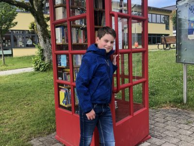 """Wilhelmsdorf Gymnasium Wilhelmsdorf  In unserer Gemeinde wurde eine original englische Telefonzelle zur Bücherzelle umfunktioniert. Eine tolle Idee, so kann ich immer stöbern und schmökern. Mit ihrem roten Farbton verleiht sie unserem Platz vor dem Rathaus den """"typical english"""" Charme! I love it!"""