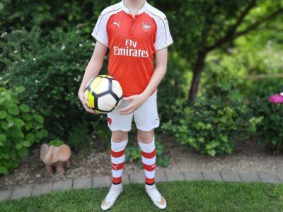 Hallo ich heiße Luis ich zeige hier ein originales Arsenal Trikot, Einen ball aus einem England Fan-Shop und ein Sparschwein mit der englischen flagge auf dem rücken   Ich bin Auf der Gesamtschule Reichshof