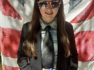 """Je suis Laodis Rochard--Poher du collège la cathédrale la salle à Angers. Aujourd'hui c'était ma journée anglaise """"The Big Challenge"""" à la maison. Je suis donc habillée comme sur la photo depuis ce matin. Pour la photo j'ai aussi utilisé ma couette, mes lunettes de soleil, et le bloc d'anglais """"une leçon par jour"""" de ma grande sœur."""