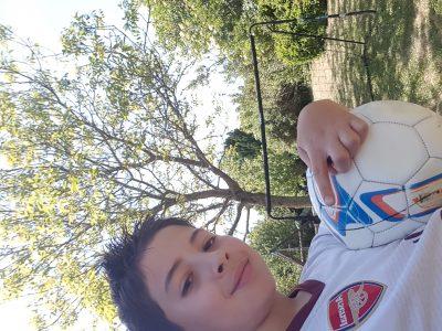 J ai pris en photo moi avec un maillot arsenal ( club de football anglais ) que j ai ramener  d'Angleterre et avec mon ballon de football aussi ramener d Angleterre avec une vue sur mon magnifique jardin
