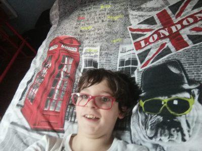 """Ville : Saverdun Collège : Girbet  La photo me représente allongé sur mon lit. La couette, qui me réchauffe bien les hivers, décrit une cabine téléphonique anglaise, un chien anglais avec des lunettes de soleil (tout le monde sait qu'il fait beau en Angleterre !!!!) et un drapeau de """"London"""".  I like England !!!! I would like to go to London.   Tom Gonzalez."""