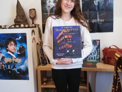 """Je vous présente un bout de ma collection Harry Potter. Le livre que je porte dans mes mains sur la photo est """" the prisoner of Azkaban"""". Ce livre, je l'ai acheté à la librairie Lello à Porto qui se situe au Portugal. Elle a inspiré J. K. Rowling pour les escaliers de la librairie """"Fleury et Bott"""" dans le Chemin de Traverse. Mon plus grand rêve serait d'aller en Angleterre avec ma famille pour visiter Londres et aller au Studio Harry Potter.  Collège DESCARTES à ANTONY"""