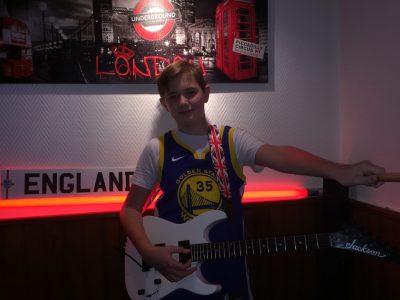 L'Anglais est représenté 4 fois sous différentes formes: Maillot de Basket-Ball américain, la sangle de la guitare avec le drapeau du Royaume-Uni, La plaque avec écrit England et le tableau londonien.