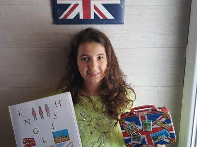 Mouthe collège de la source.  Une photo de moi avec se que j'ai trouvé :avec une valise de Londres (London), une pochette avec un drapeau d'Angleterre et mon cahier d'anglais.